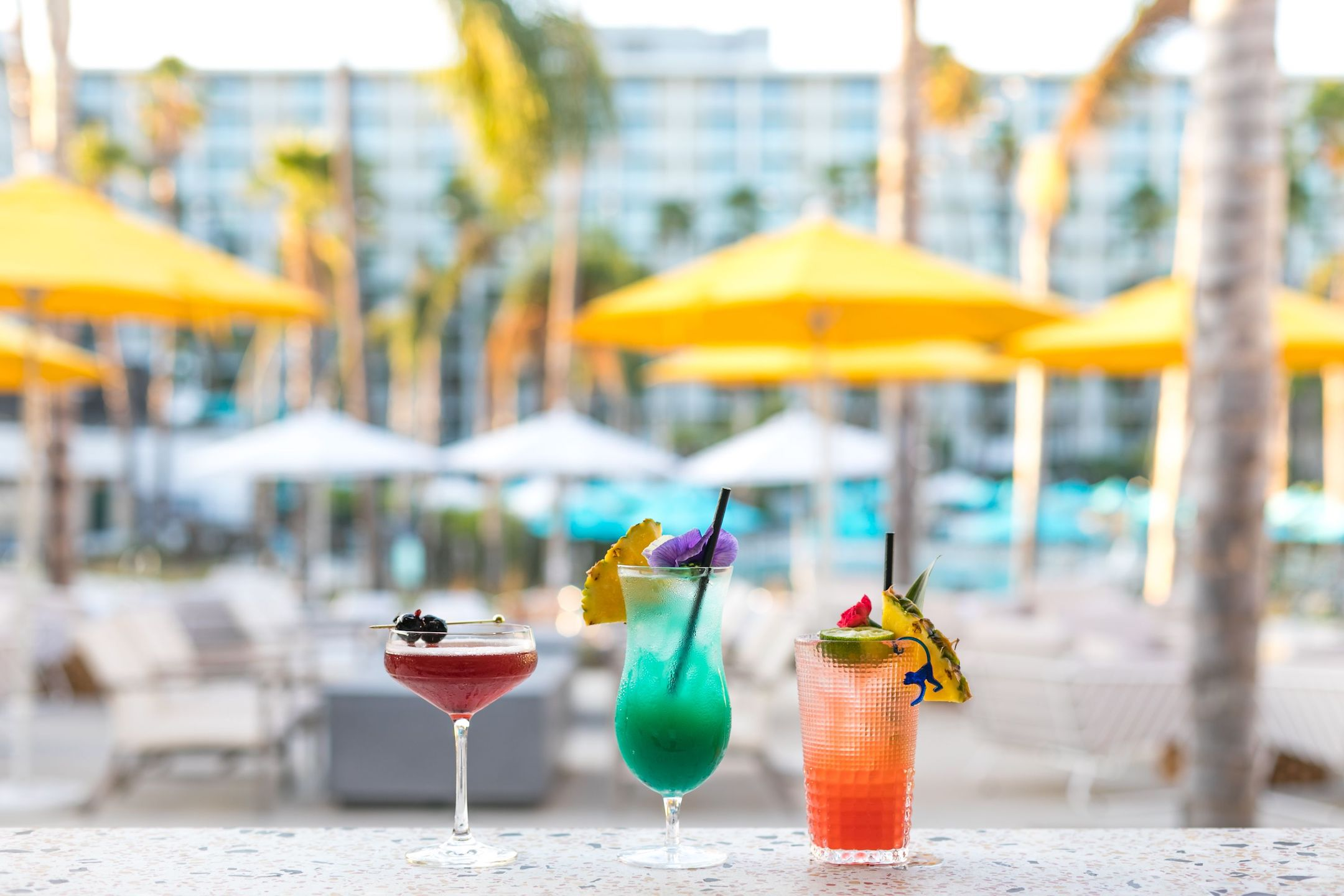 3 colorful drinks sitting on a table at a landmark resort.