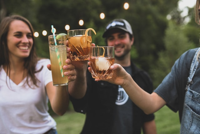 people toasting with drinks made with alcohol