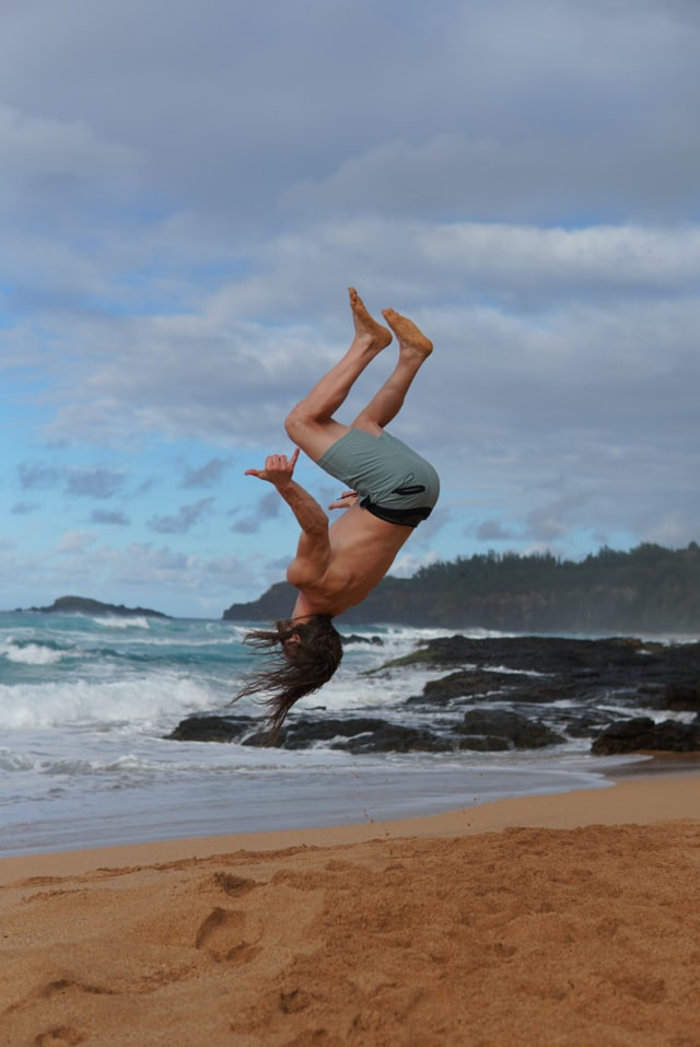 man doing a flip on a Hawaiian Beach
