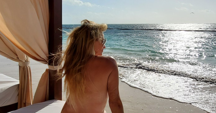 woman sitting naked on a beach