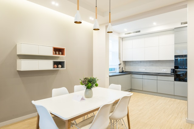 Modern kitchen and dining room with elements and furniture in white color.