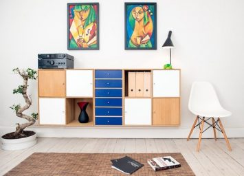 A room decorated with Wooden board in brown, white, and blue color with interesting artwork above it showing How to Use Colors in Your Home Design
