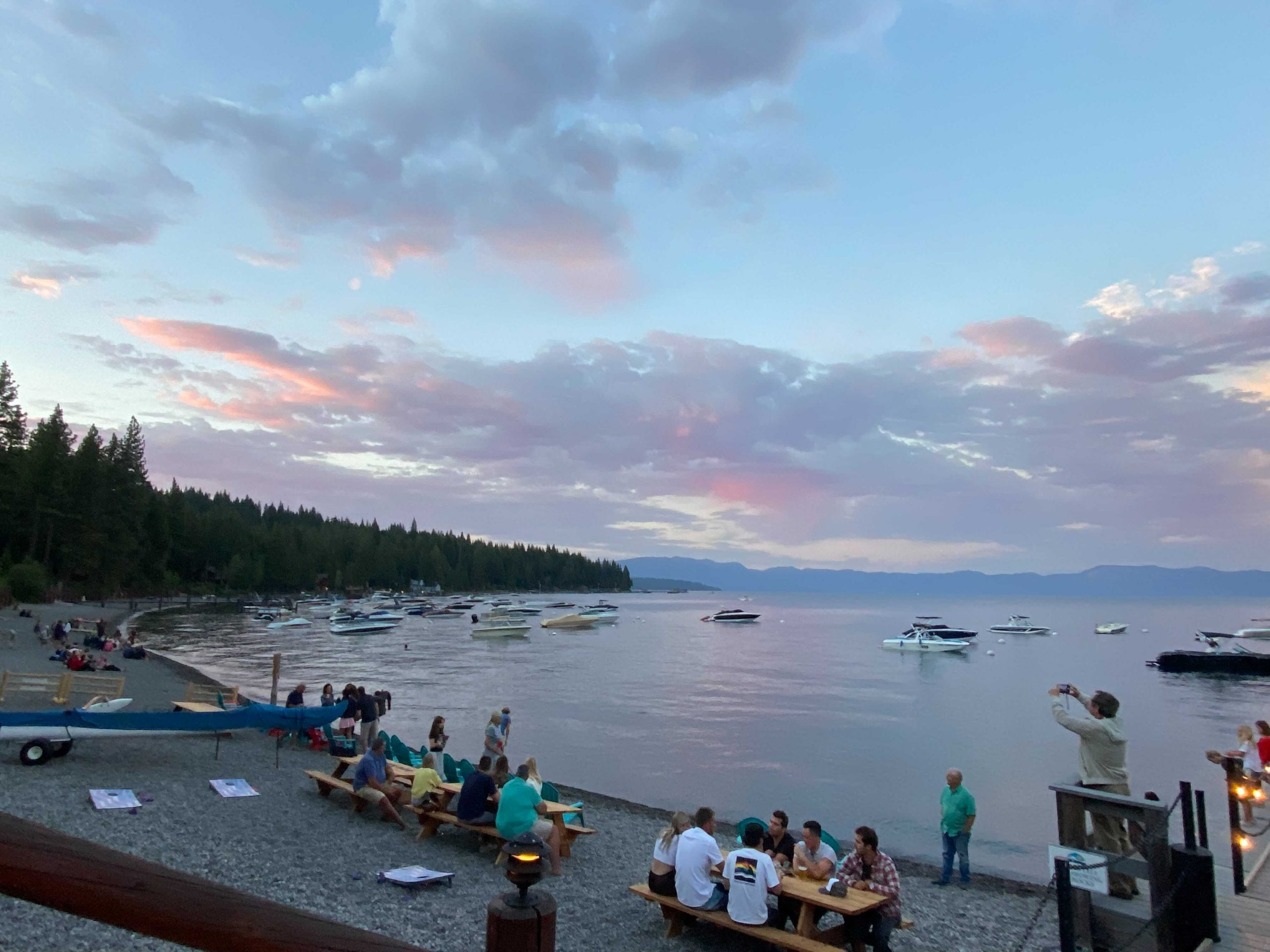 picture of the sunset over the Sunnyside marina with people sitting around eating in Lake Tahoe