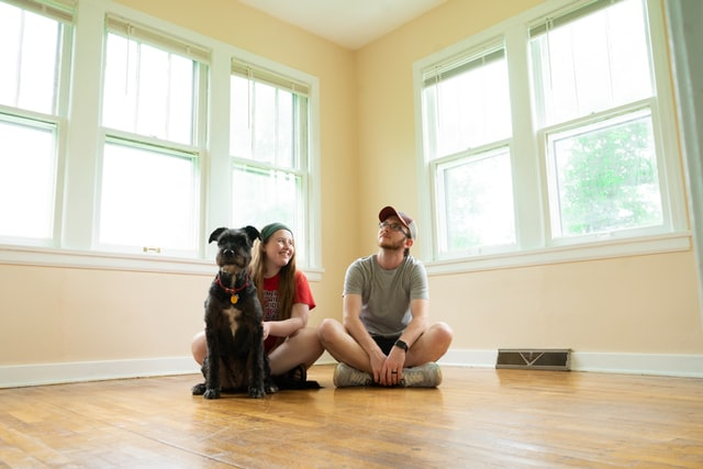 Couple with dog thinking how to make their new place feel like home.