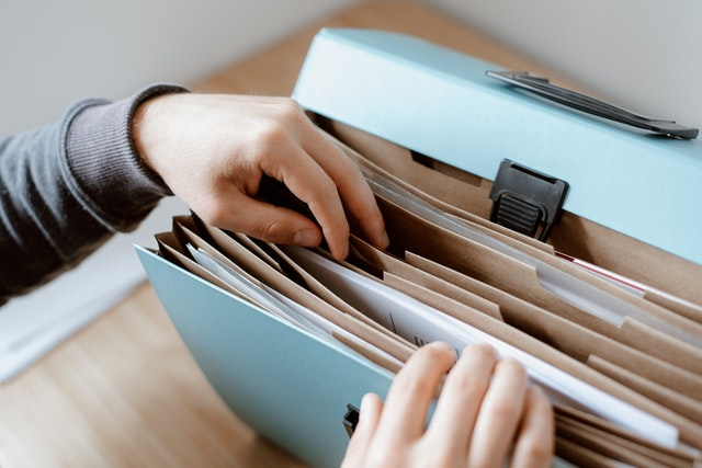 A person going through documents in a folder.