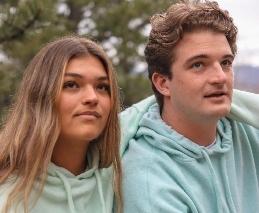 two people wearing hoodies