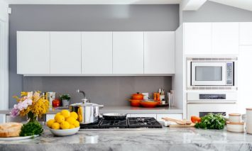 A modern white kitchen with a marble countertop