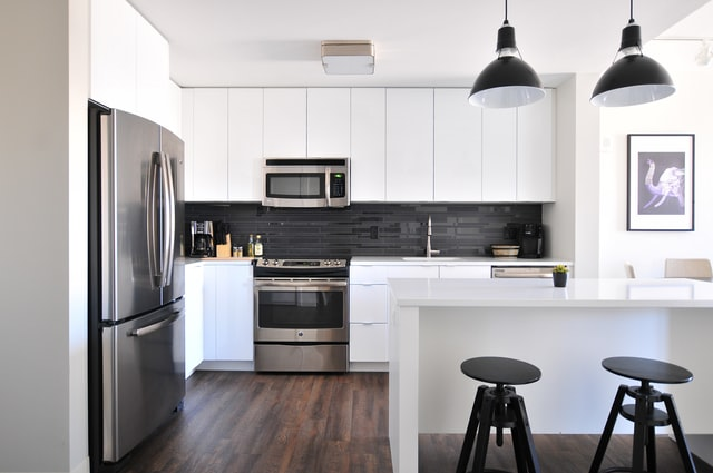 A white kitchen with black fridge and bar chairs