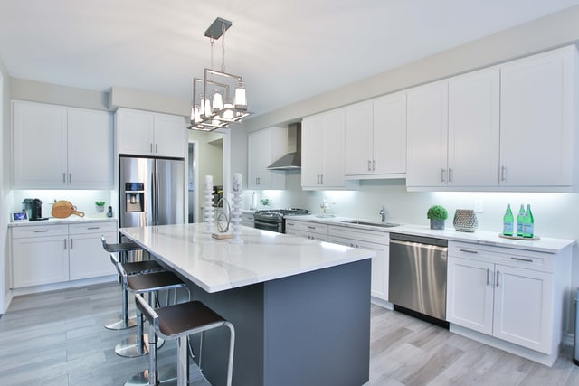A large bright kitchen with a kitchen island and chairs in the middle