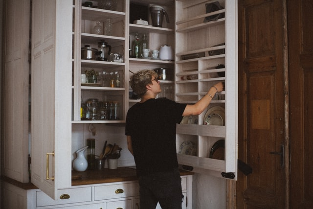 A person looking into a pantry cupboard